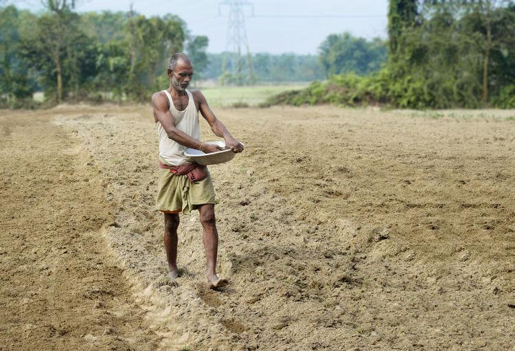 Full length of shirtless man standing on dirt road
