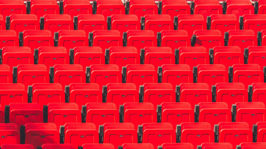 Full frame shot of empty red chairs at stadium