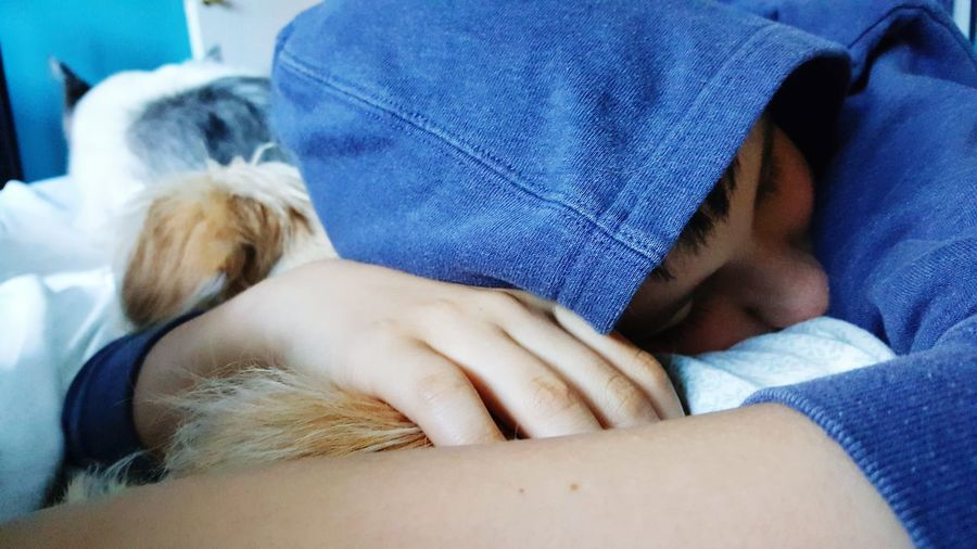 Pet owner sleeping on bed holding puppy