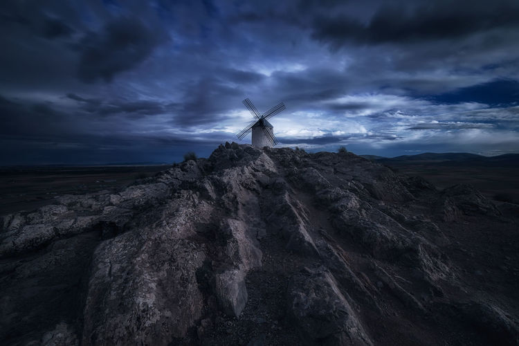 Wind turbines on rocks by sea against cloudy sky