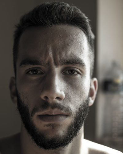 Close-up portrait of bearded man at home