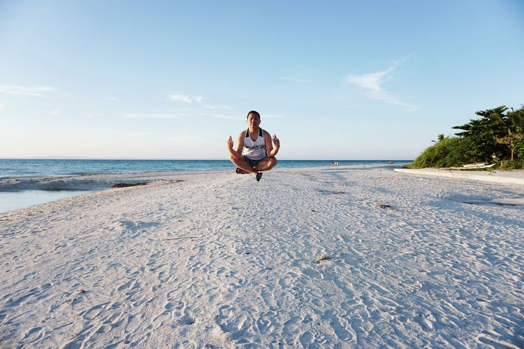 Man meditating on beach against sky