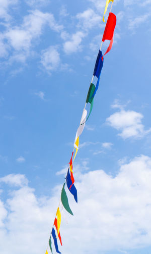Many colorful flags against a blue sky Sky Flags Bunting Blue Colorful Flag Triangle Party Banner Background Sunny Prayer Happy Event Fair Outside Bright Fun Day Wind String Carnival Summer White Celebration Cloud - Sky Low Angle View Multi Colored No People Nature Hanging Variation Pole Environment Outdoors Decoration Patriotism Choice