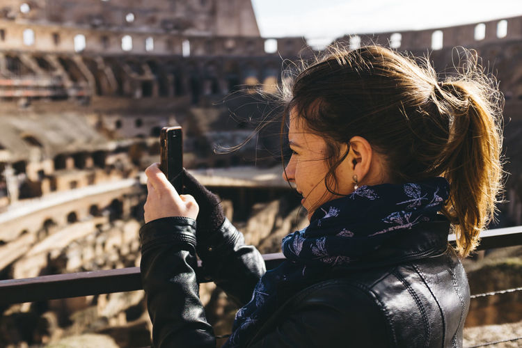 Woman photographing coliseum through smart phone