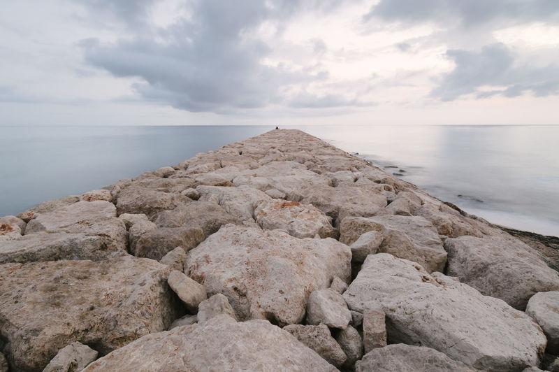 Rocky Pier In Sea Against Sky