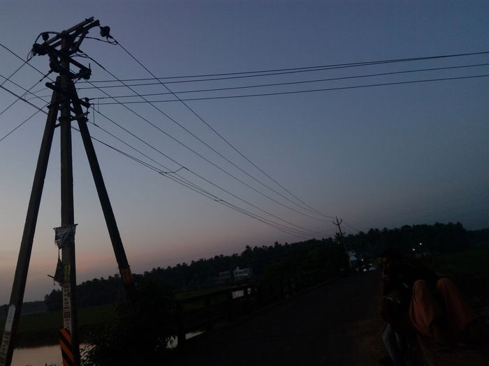 electric line at sunset The Week on EyeEm From My Point Of View Low Angle View Mobilephotography Exceptional Photographs Simple Quiet Love The Purist (no Edit, No Filter) Enchanting India EyeEm Selects Hello World Check This Out ASIA Simple Photography Low Light Electricity  Urban Skyline Rural Sunset Blue Cable Electricity  Technology Power Supply Electricity Pylon Bird No People Sky Outdoors Day