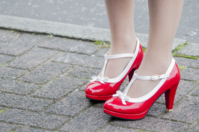 Low section of bride wearing red shoes standing outdoors