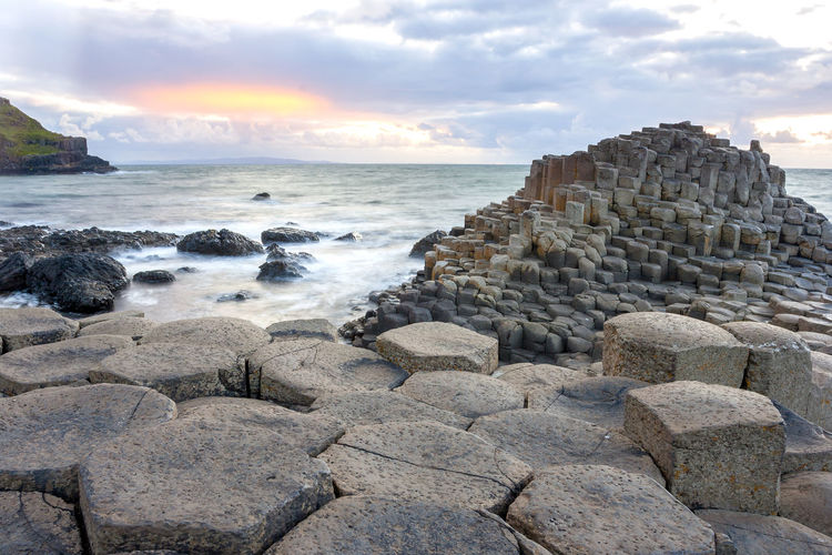 Sunset at Giant s Causeway in North Antrim, Northern Ireland Sea Rock Solid Water Sky Rock - Object Cloud - Sky Beach Beauty In Nature Land Scenics - Nature Nature Motion Horizon Over Water No People Horizon Wave Tranquil Scene Rock Formation Outdoors Breaking Rocky Coastline