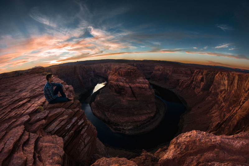 Hiker Sitting On Rock Formation Horseshoe Bend
