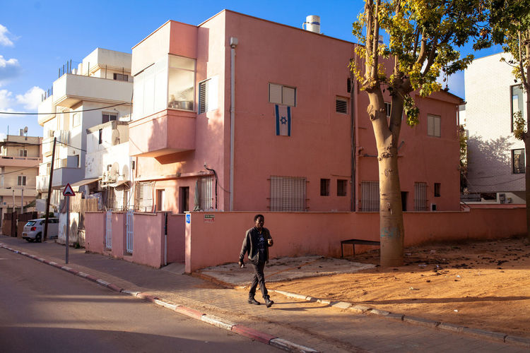 © Adlan Mansri Adventures In The City Architecture Building Building Exterior Built Structure City Day Footpath Full Length Men Nature One Person Outdoors Real People Rear View Residential District Road Street Sunlight Transportation Walking