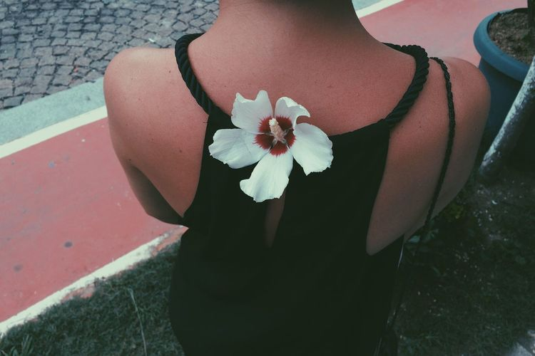 Midsection of woman wearing white flower on back