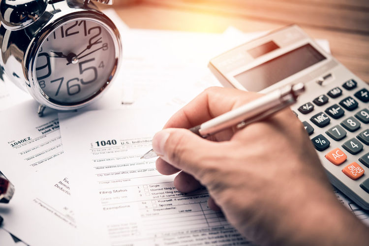 Number Calculator Human Hand Hand Paper Finance Selective Focus Real People Human Body Part Indoors  Business People Table Text Finger High Angle View Accuracy Pen Document Calculating Paperwork