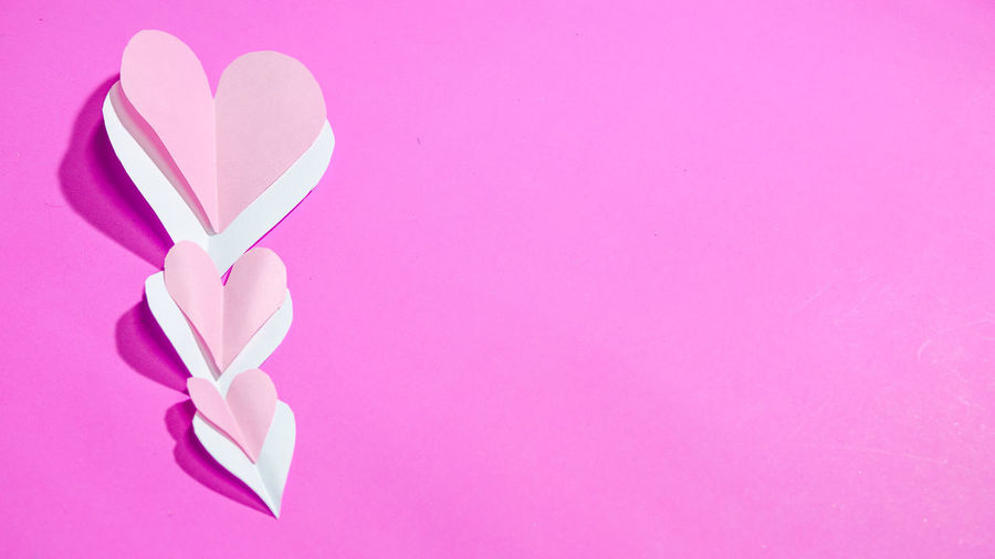 Directly above shot of pink heart shape against purple background