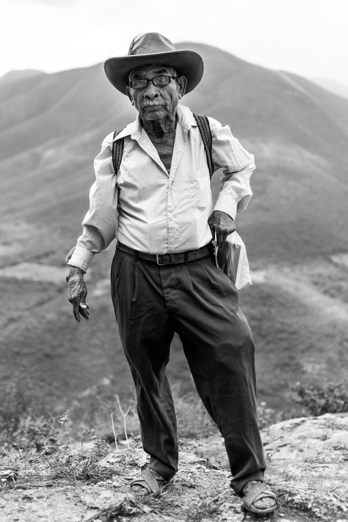 PORTRAIT OF MAN STANDING AGAINST MOUNTAIN