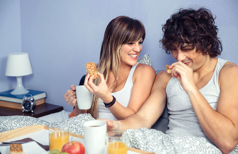 Couple having breakfast on bed at home