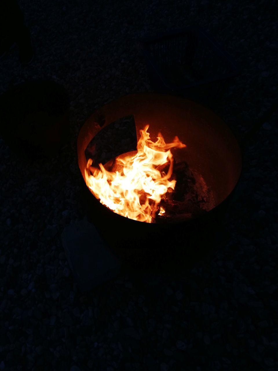 HIGH ANGLE VIEW OF FIRE BURNING IN THE DARK