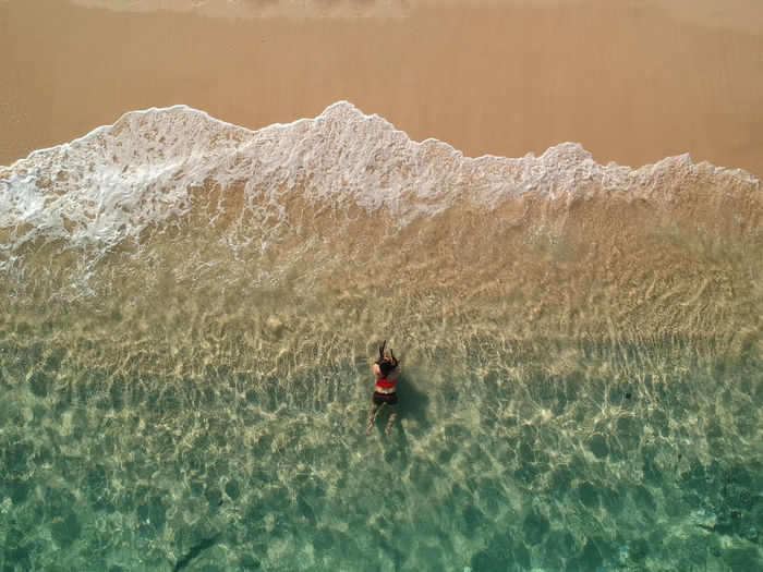Aerial view of woman on shore at beach