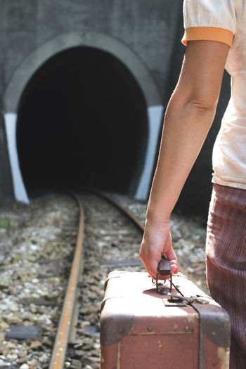 Midsection of woman with suitcase standing on railroad track