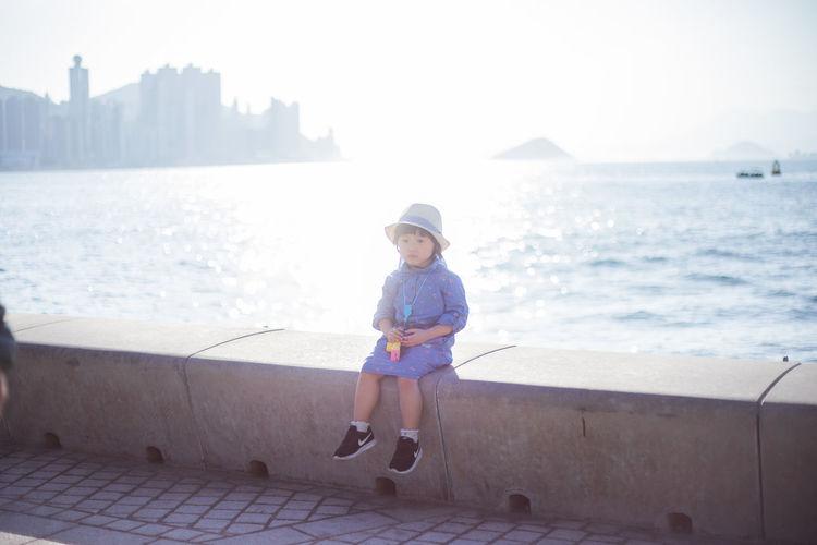 Portrait of boy on sea shore against sky