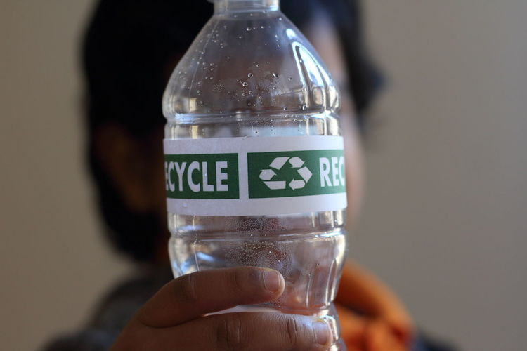 Close-up of person holding plastic bottle