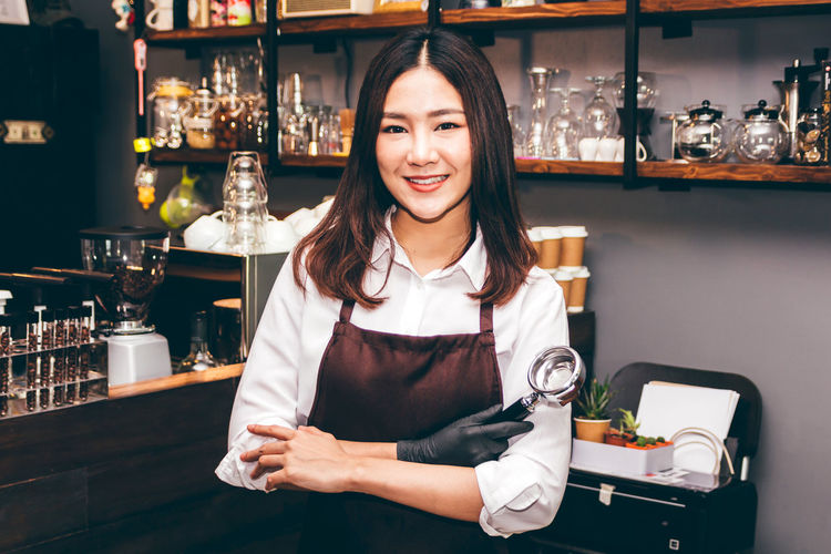 Barista in coffee shop Bar - Drink Establishment Bar Counter Bartender Business Drink Emotion Food And Drink Front View Glass Hair Hairstyle Happiness Holding Indoors  Looking At Camera Occupation One Person Portrait Real People Refreshment Service Occupation Smiling Standing Waist Up Young Adult