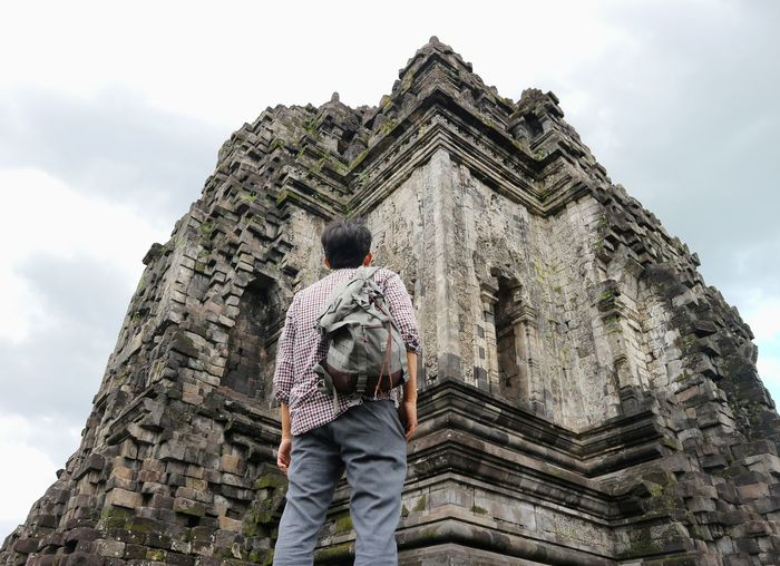 Low angle view of man looking at temple