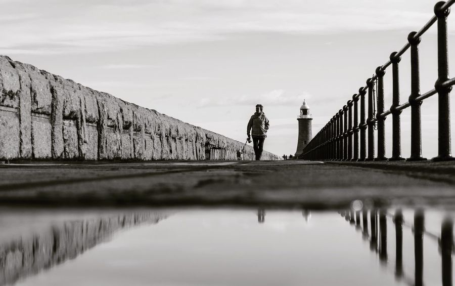 Tunemouth Pier - Nikon Lighthouse Reflection Northeast EyeEm Masterclass The Week on EyeEm Blackandwhite Nikon Pier Railing Full Length One Person Walking Real People Water Bridge - Man Made Structure Sky Outdoors Nature Architecture