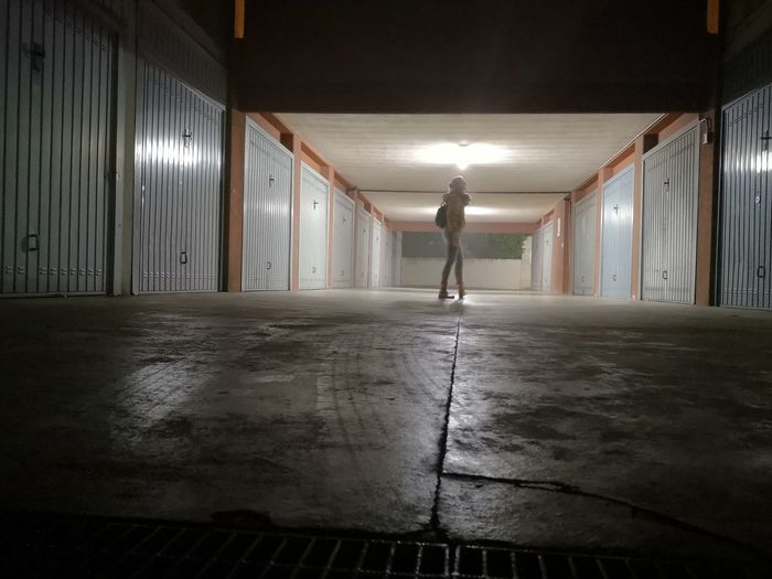 Rear view of man walking in illuminated building