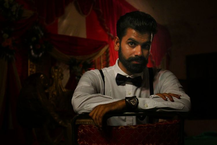 Portrait of bearded young man sitting at home