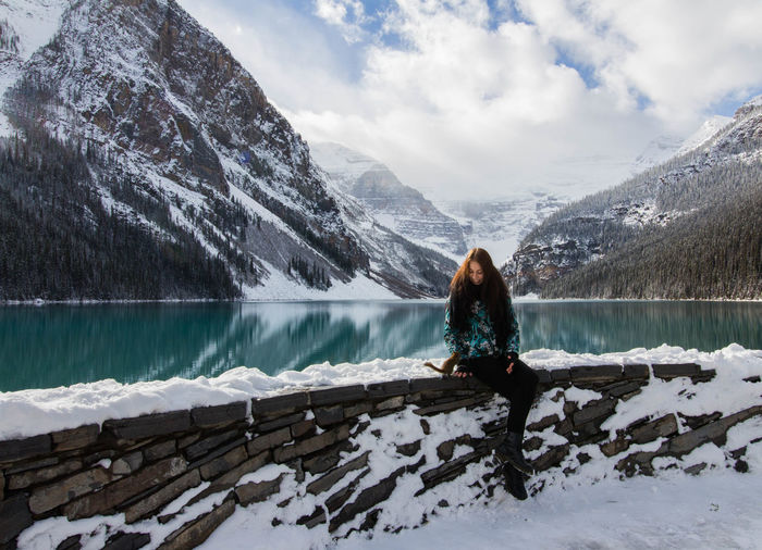 Woman sitting by lake against mountain during winter