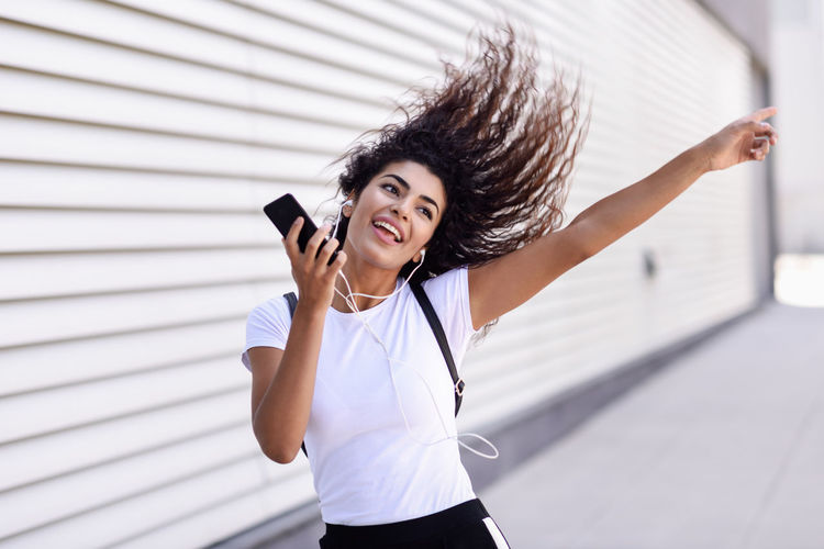 Happy woman listening music while dancing by wall in city