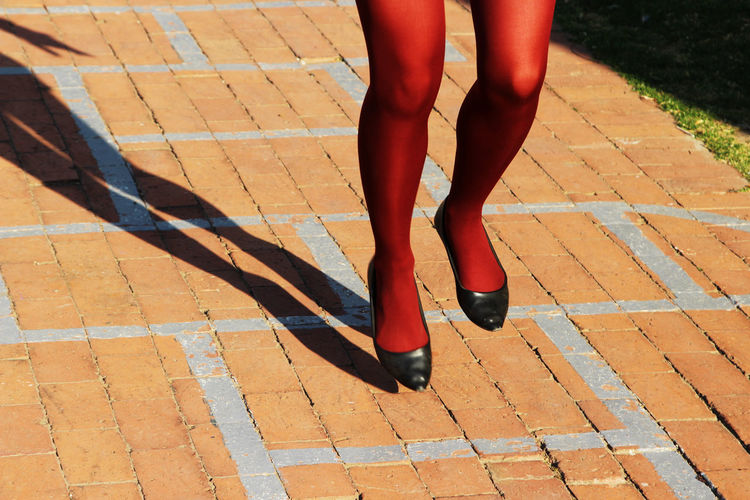 A women playing hop scotch on a playground. This image has selective focusing. Expressive Fun Stockings Youthful Days Day Hop Scotch Human Body Part Human Leg Joy Leisure Activity Lifestyles Low Section One Person Outdoors Passionate People Real People Recapturing Youth Red Standing Women Women Around The World Youthful Hearts