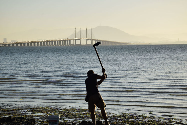 Rear View Of Man Digging With Garden Hoe At Riverbank Against Bridge During Sunset
