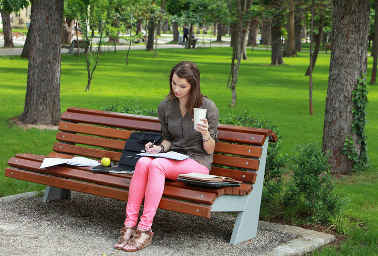 Woman studying outside on a bench in an urban park. Sitting Park Bench Real People Casual Clothing One Person Park - Man Made Space Young Adult Lifestyles Park Bench Outdoors Woman Young Woman Writing Learning Student Student Life Nature person Attention
