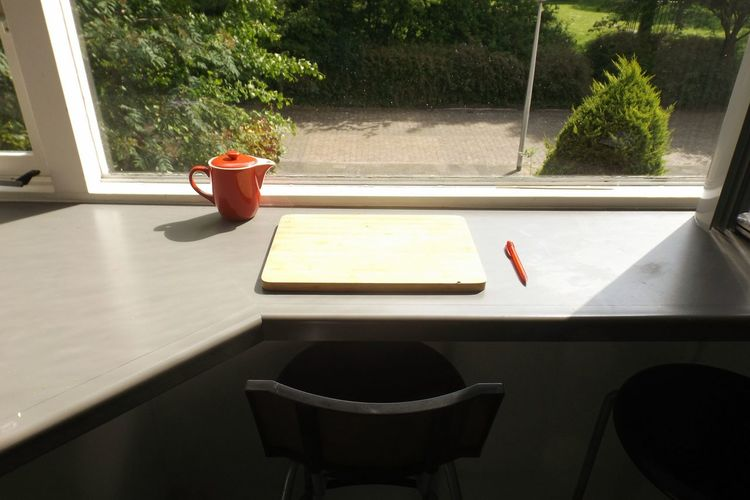 High Angle View Of Cutting Board And Teapot Against Window On Table