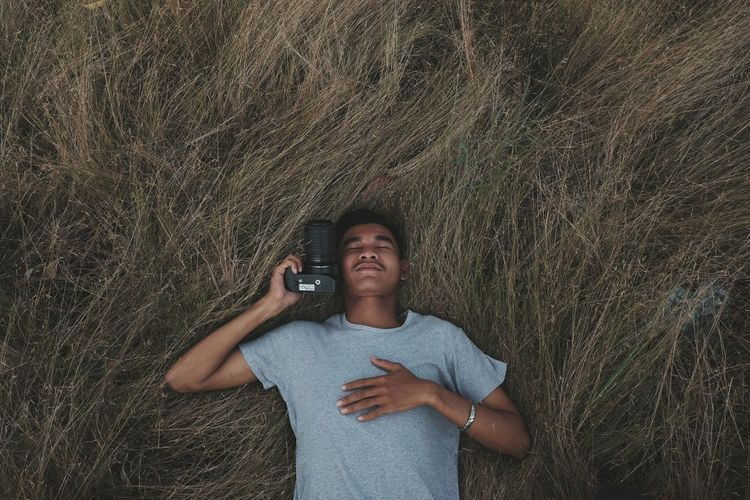 Man with camera lying down on hay