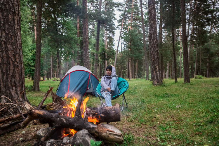 Woman Sitting By Campfire In Forest