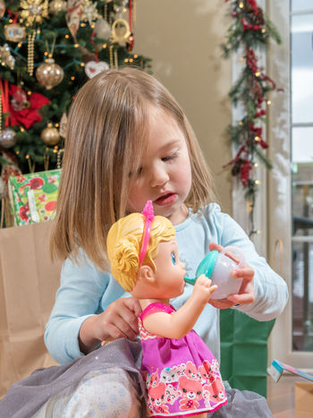 Happy preschool toddler with christmas gifts and presents and feeding her doll Christmas Doll Dolly Feeding  Happy Imagination Preschool Age Presents Xmas Child Childhood Cute Drinking Gift Girl Make Believe Parcel Playing Portrait Pretty Real People Toddler  Unwrapping