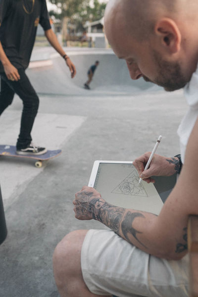 Artist Skateboarding Adult Close-up Day Drawing Holding Human Hand Ipad Ipad Pro Low Section Men Outdoors Paper People Real People Tattoo Tattoos Two People Writing Young Adult
