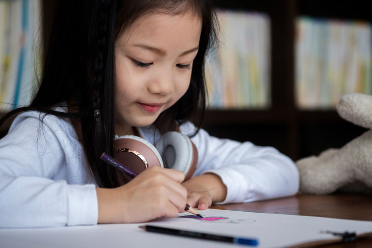 Close-Up Of Girl Writing On Book At Desk
