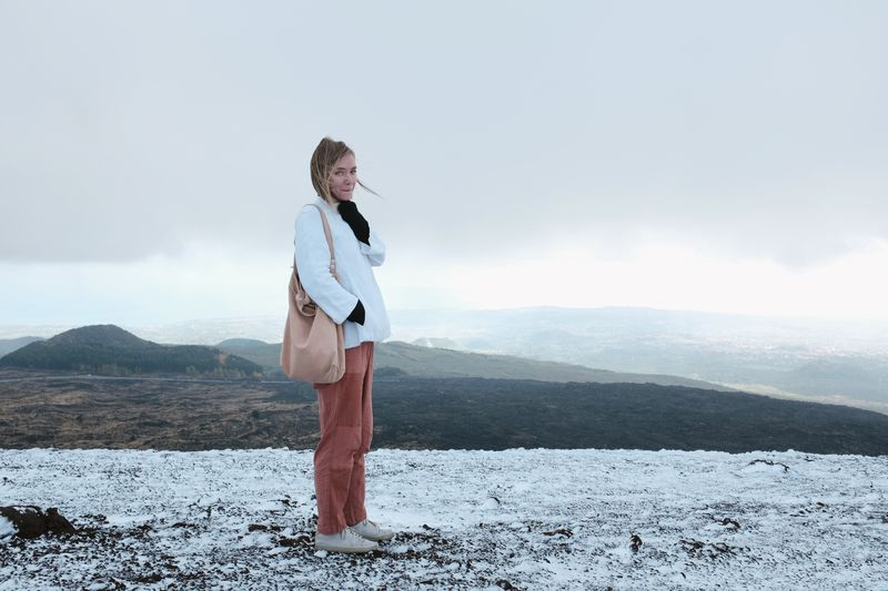 Portrait of young woman standing on snow covered field against mountains