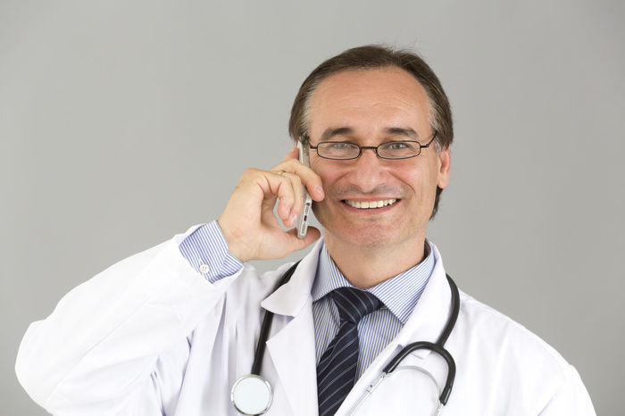 Diagnosis Smiling Reassure Self Confidence Self Confident Good News Medical Team Man With Glasses Talking On The Phone Speaking On The Phone Posing Front View Looking To The Camera Looking At Camera White Background Clinic Doctor  Pediatrics Hospital Portrait Medical Stethoscope  Pediatrician Reassurance Reassuring