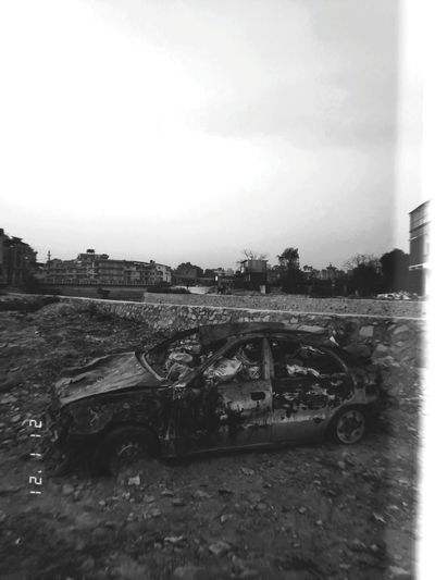 Abandoned car against sky
