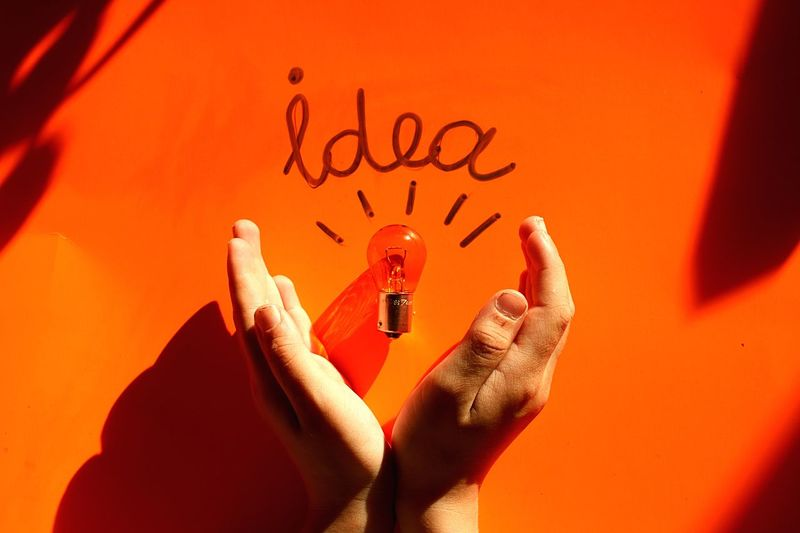 Cropped Hands With Light Bulb And Idea Text On Orange Table