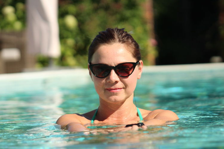 Portrait of mid adult woman wearing sunglasses while swimming in pool