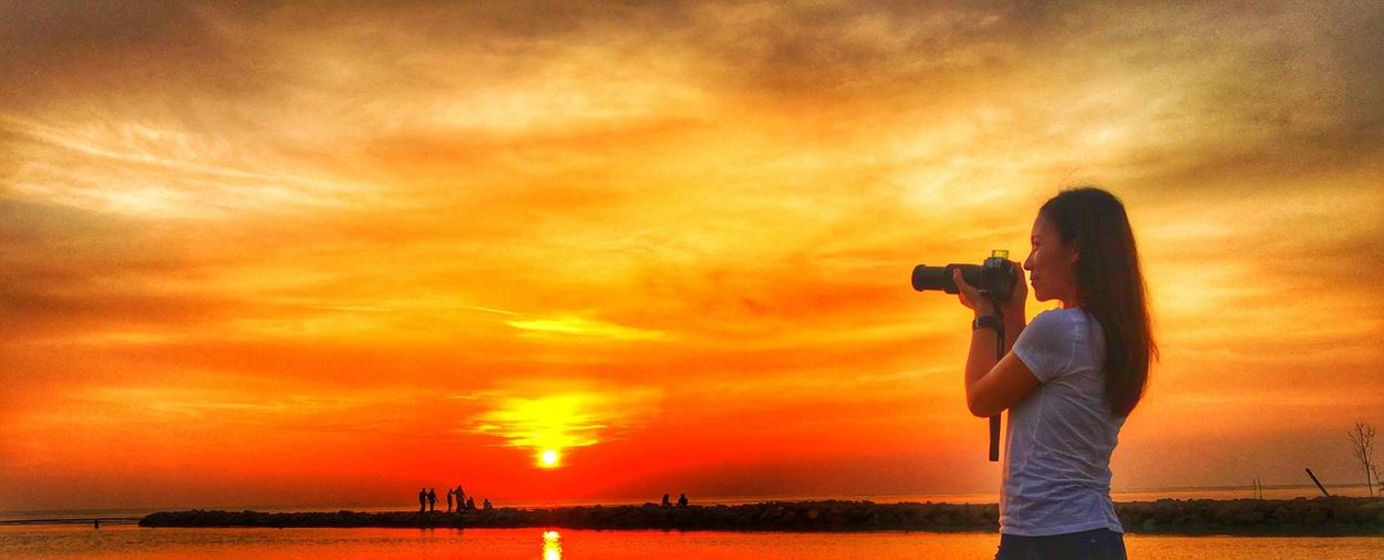 Sunset Sky Photography Themes Beauty In Nature Nature Sea Real People Camera - Photographic Equipment Cloud - Sky Scenics Men Standing Technology Outdoors Tranquil Scene Leisure Activity Tranquility Digital Camera Water