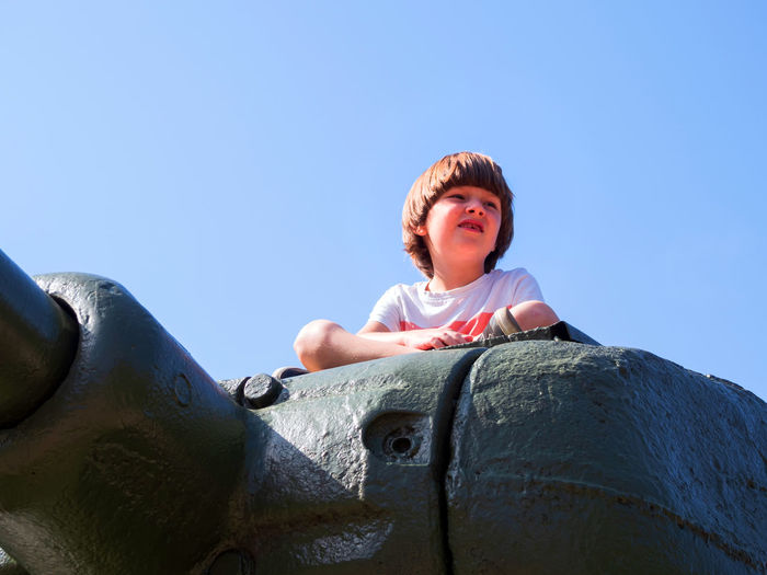 Low angle view of boy against clear sky