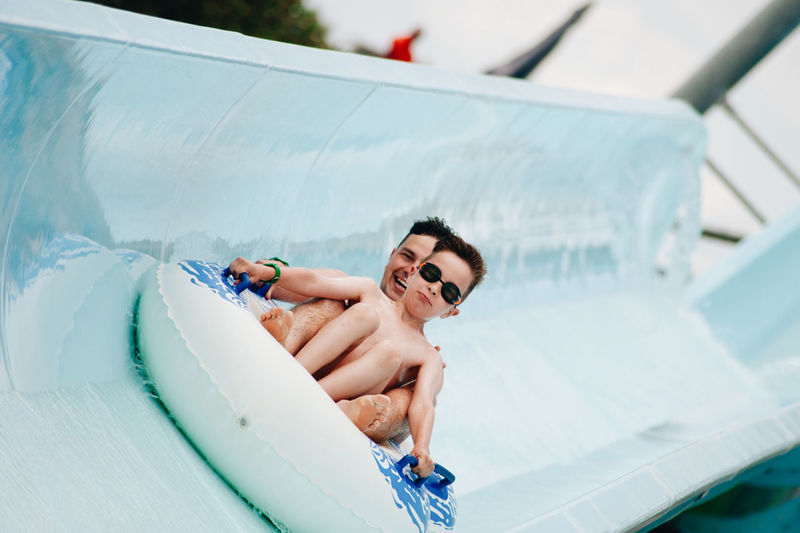 Cheerful father and son enjoying at water park