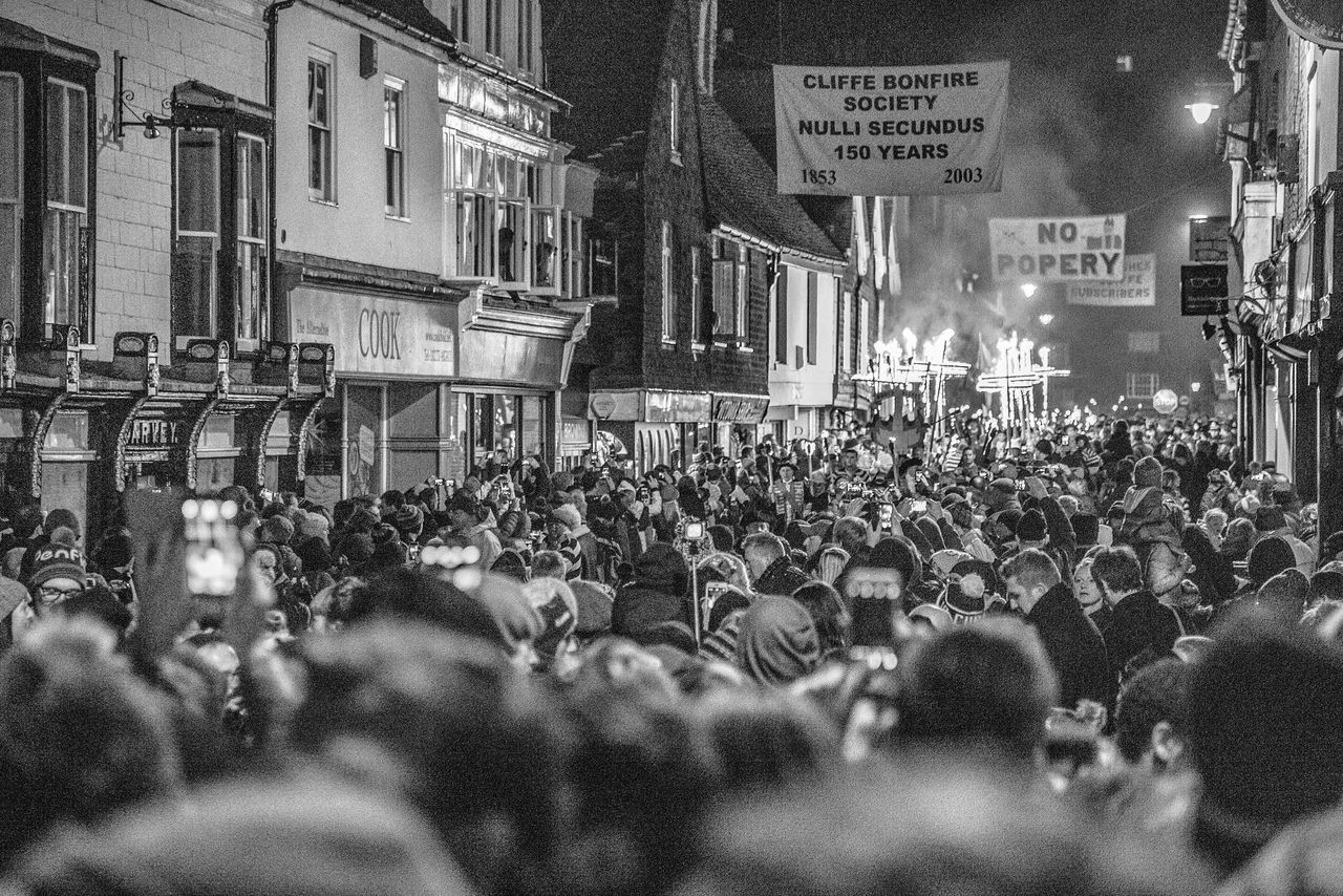 large group of people, building exterior, crowd, architecture, protestor, real people, men, night, built structure, women, city, outdoors, people, riot, adult