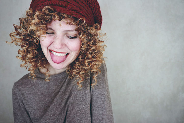 Smiling Young Woman Sticking Out Tongue Against Wall